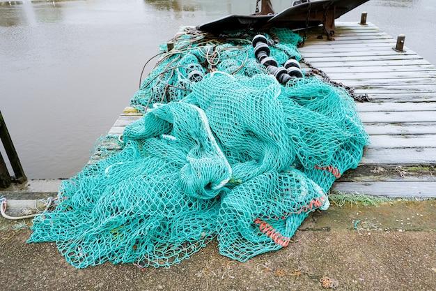 Niebieska sieć rybacka na pontonie z linami i pływakami pokrytymi porannym szronem