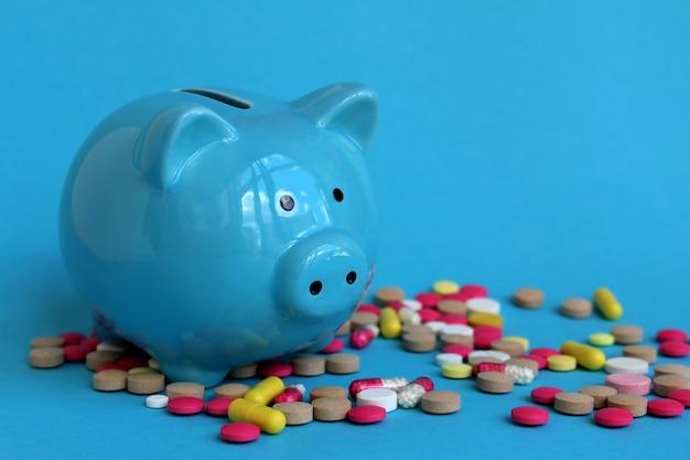 Niebieska skarbonka świnia stoi na jasnych tabletkach na niebieskiej ścianie. temat biznes, finanse i zdrowie.
