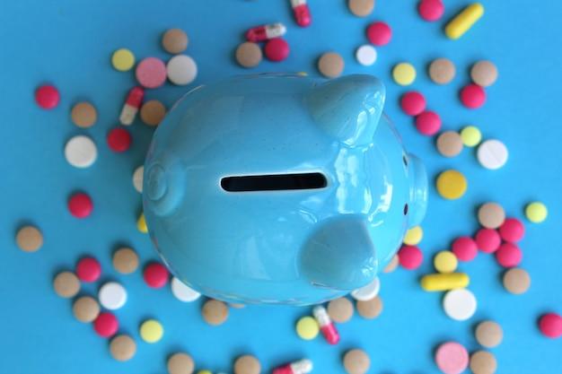 Niebieska skarbonka świnia stoi na pigułkach na niebieskiej ścianie. temat medycyny, zdrowia i finansów. widok z góry.
