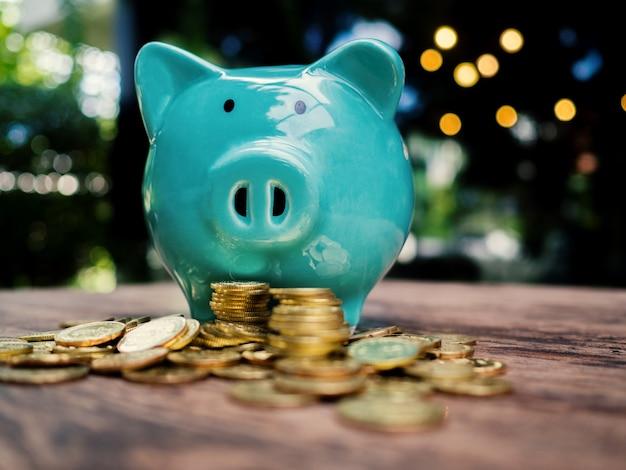 Niebieska skarbonka ze stosem złotych monet oszczędzanie pieniędzy na przyszły plan inwestycyjny i fundusz emerytalny