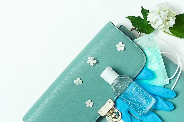 Niebieska skórzana torebka damska z maską medyczną, środkiem dezynfekującym i rękawiczkami.