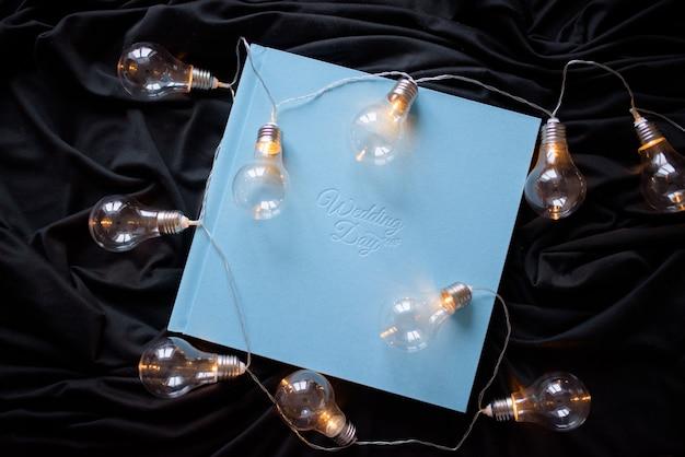"""Niebieska ślubna fotoksiążka z napisem """"dzień ślubu"""" na czarnej tkaninie. wokół rozłożona girlanda retro."""