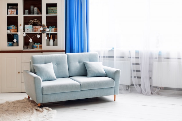 Niebieska sofa w białym nowoczesnym wnętrzu z ozdób choinkowych.