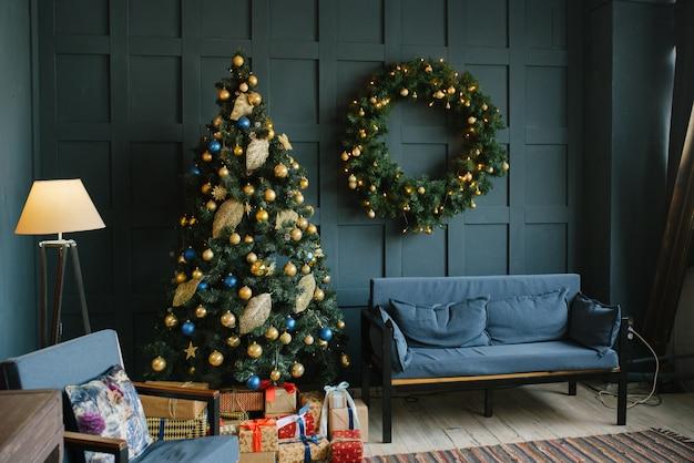 Niebieska sofa z poduszkami i świąteczny wieniec na ścianie w salonie w stylu loftu.
