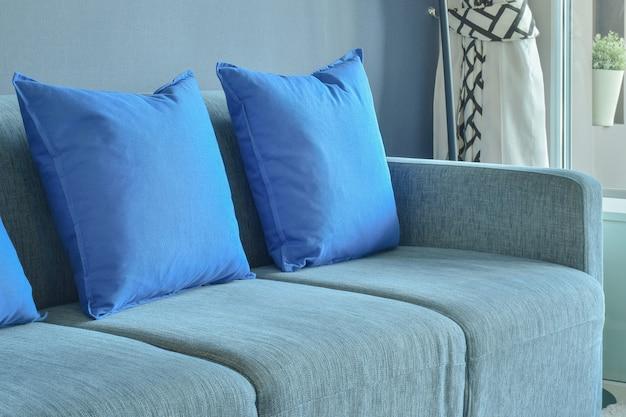 Niebieska sofa z rzędem niebieskich poduszek w salonie