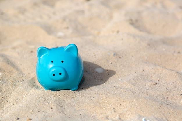Niebieska świnia skarbonka na ciepłym drobnym piasku morskim oszczędności na wakacjach.