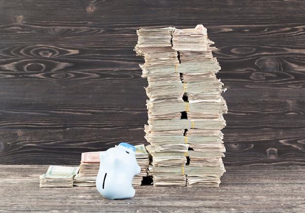 Niebieska świnka oszczędza, wspina się na wysoki pakiet pieniędzy,