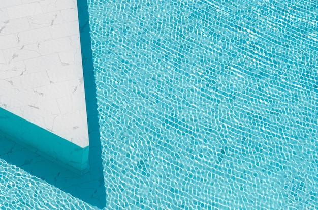 Niebieska szarpana woda w basenie wykonanym z białej marmurowej płytki kamiennej.