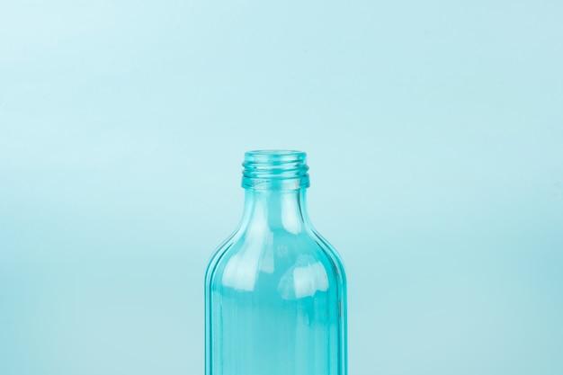 Niebieska szklana butelka. na białym tle na niebieskiej powierzchni. koncepcja pojemników wielokrotnego użytku