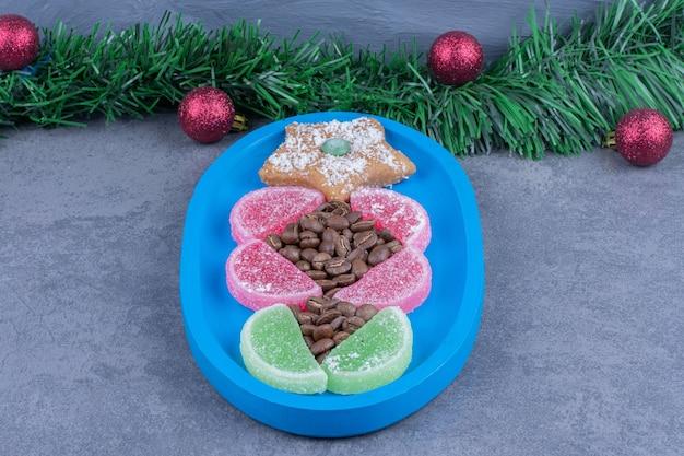 Niebieska tablica z gwiazdką ciasteczka i słodkimi żelkami