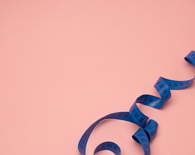 Niebieska taśma centymetrowa zwinięta w spiralę na różowym tle