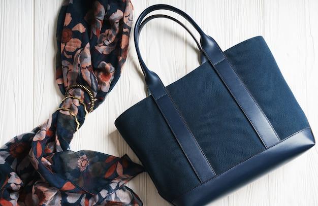 Niebieska torebka i szalik z złote akcesoria na drewnianej białej powierzchni