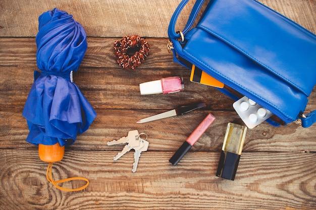 Niebieska torebka, parasolka i akcesoria damskie. rzeczy z otwartej damskiej torebki. widok z góry. stonowany obraz.