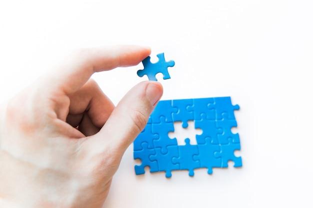 Niebieska układanka w ręku. ręka trzyma kawałek układanki. łączenie puzzli, połączenie biznesowe, edukacja, społeczeństwo i praca zespołowa