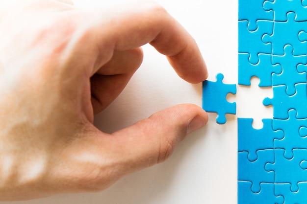 Niebieska układanka w ręku. ręki mienia łamigłówki kawałek na białym tle. łączenie puzzli, połączenie biznesowe, edukacja, społeczeństwo i praca zespołowa