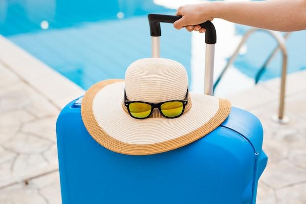 Niebieska walizka, czapka i okulary przeciwsłoneczne w pobliżu basenu