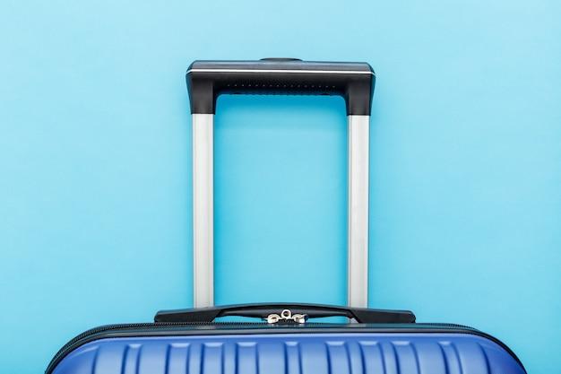 Niebieska walizka na niebieskim tle koncepcji podróży.