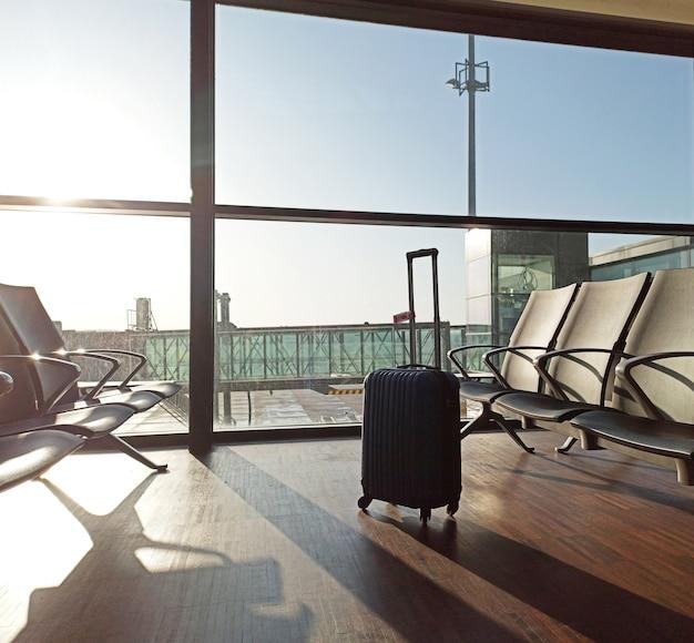 Niebieska walizka na pustym lotnisku. poczekalnia anulowanie opóźnienia lotu. podróże i wakacje