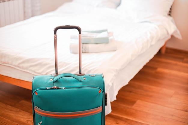 Niebieska walizka podróżna w sypialni.
