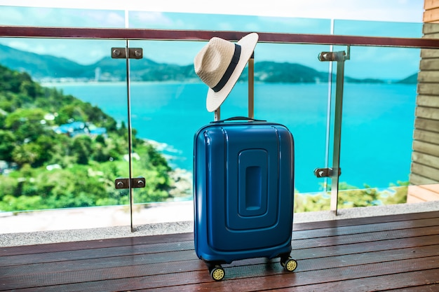 Niebieska walizka podróżna z czapką stojącą na otwartym balkonie z widokiem na morze i piękną przyrodę. wakacje i podróże