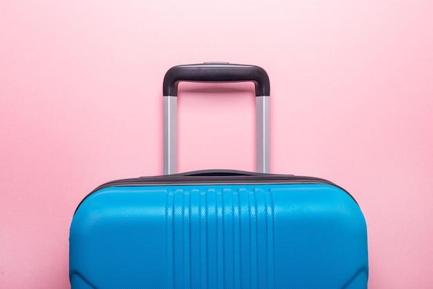 Niebieska walizka w pastelowym różu. kreatywne wakacje letnie, wakacje, koncepcja podróży