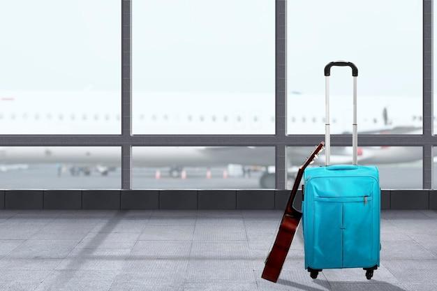 Niebieska walizka z gitarą na terminalu lotniska