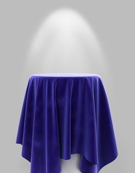 Niebieska welurowa tkanina na okrągłym cokole na szarym tle z podświetleniem