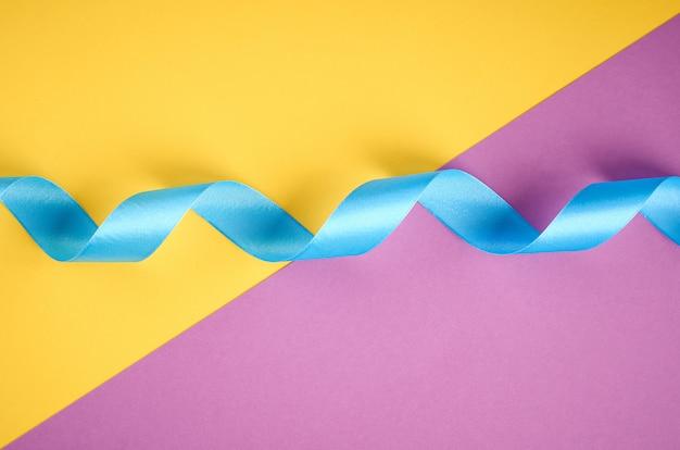 Niebieska wstążka na fioletowo-żółtej kompozycji, płaski układ