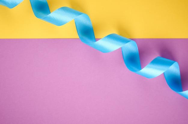 Niebieska wstążka na fioletowym i żółtym tle z copyspace, płaskie świeckich