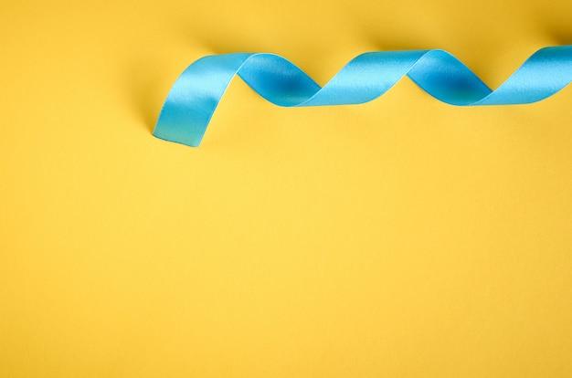 Niebieska wstążka na żółtym tle z copyspace, płaskie świeckich