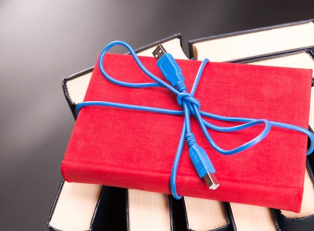 Niebieska wstążka z kabla usb na czerwonej księdze