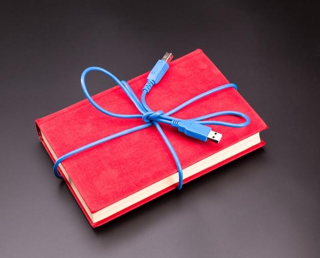 Niebieska wstążka z kabla usb na książeczce w prezencie