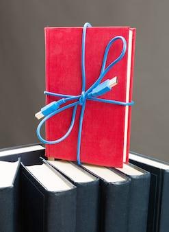 Niebieska wstążka z kabla usb na stojącej książce