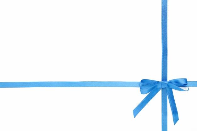 Niebieska wstążka z kokardą jako prezent na białym tle na białym tle. widok z góry.