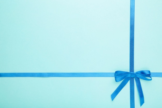 Niebieska wstążka z kokardką jako prezent na niebieskiej pastelowej powierzchni