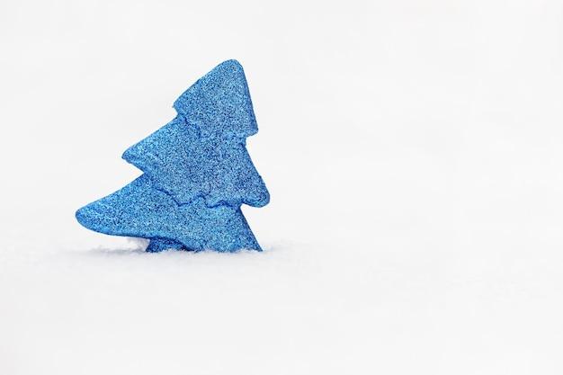 Niebieska zabawka drzewo na prawdziwym śniegu w zimowy dzień.