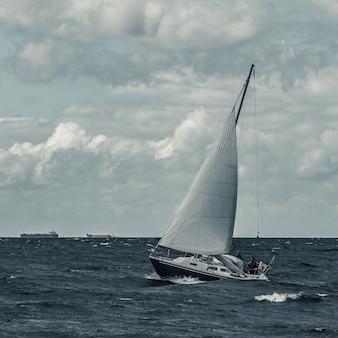 Niebieska żaglówka w podróży na wzburzonym morzu