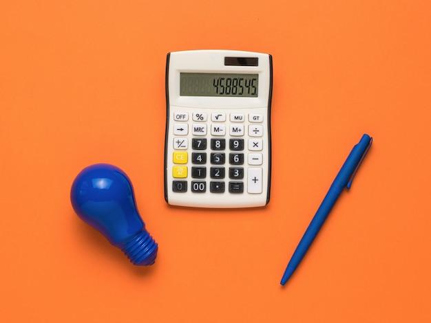 Niebieska żarówka, niebieski długopis i kalkulator na pomarańczowym tle.