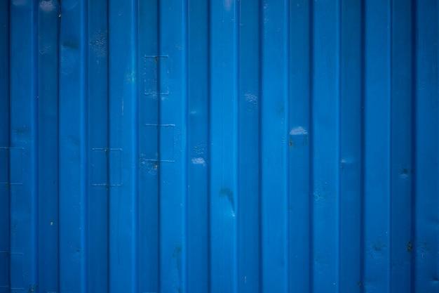 Niebieska zmarszczka ściany pojemnika wygląda jak fale na fakturze dachu cynkowego.