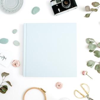 Niebieski album ze zdjęciami rodzinnymi lub ślubnymi liść eukaliptusa, aparat retro i suche pąki róży na białym tle