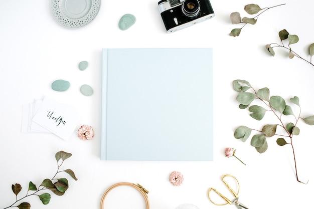 Niebieski album ze zdjęciami rodzinnymi lub ślubnymi, liść eukaliptusa, aparat retro i suche pąki róży na białym tle