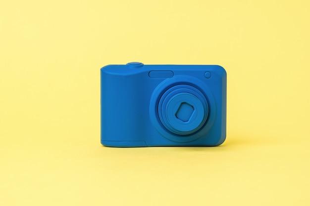 Niebieski aparat z wysuwanym obiektywem na żółtym tle. przestarzały sprzęt fotograficzny.