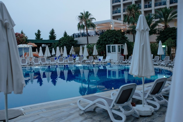 Niebieski basen z parasolami i leżakami hotelowego indyka