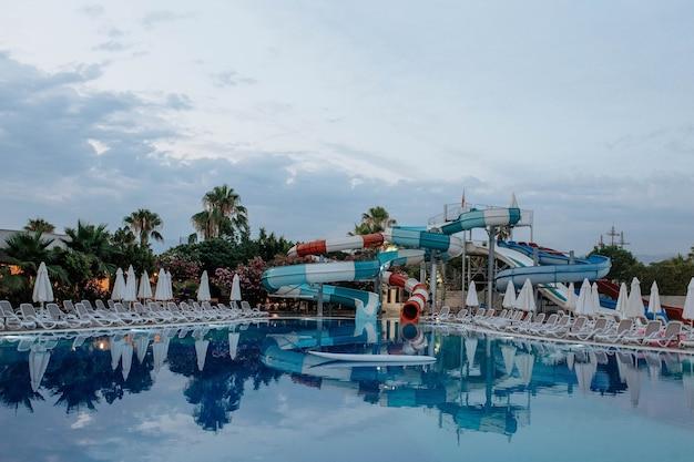Niebieski basen ze zjeżdżalniami wieczorem koncepcja turystyki i rekreacji w pięciogwiazdkowym hotelu