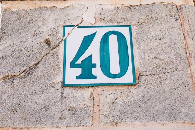 Niebieski biały numer domu czterdzieści 40 na starej ścianie wieku