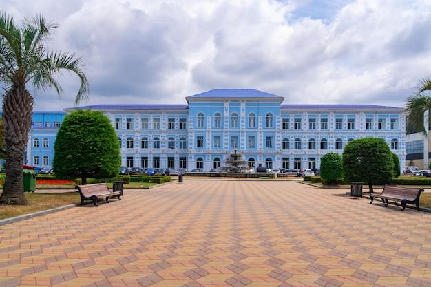 Niebieski budynek uniwersytetu państwowego w batumi i fontanna przed nim.