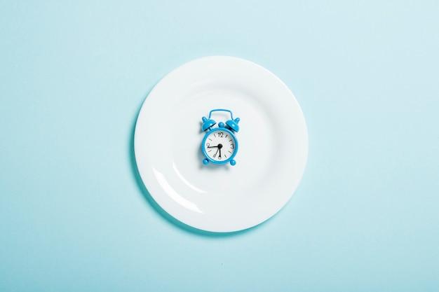 Niebieski budzik leży na białym talerzu na niebieskiej ścianie. pojęcie diety, harmonogram posiłków, utrata masy ciała. leżał płasko, widok z góry