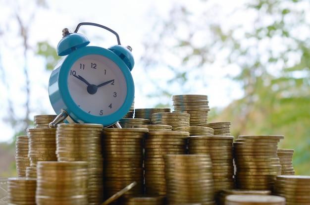 Niebieski budzik na dużej ilości błyszczących starych stosów monet ukraińskich 1 hrywna z bliska na tle niewyraźne zielone drzewa. koncepcja planowania finansowego i zarządzania czasem biznesowym