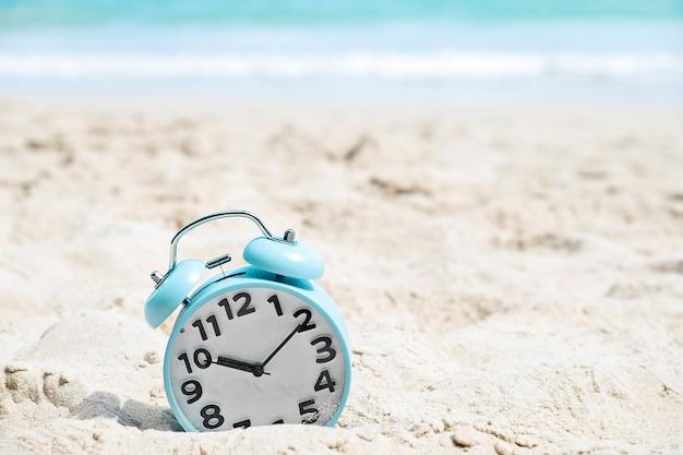 Niebieski budzik na piaszczystej plaży nad morzem