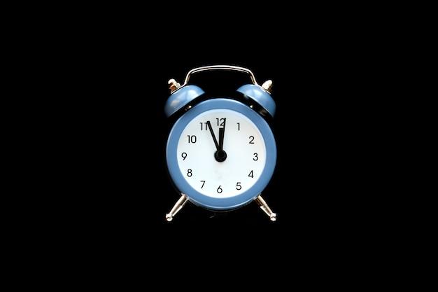 Niebieski budzik vintage pokazuje godzinę 12 na białym tle na czarnym tle. obudź się i pospiesz się. gorąca wyprzedaż, ostateczna cena, ostatnia szansa. odliczanie do północy nowego roku. skopiuj miejsce na twój tekst.
